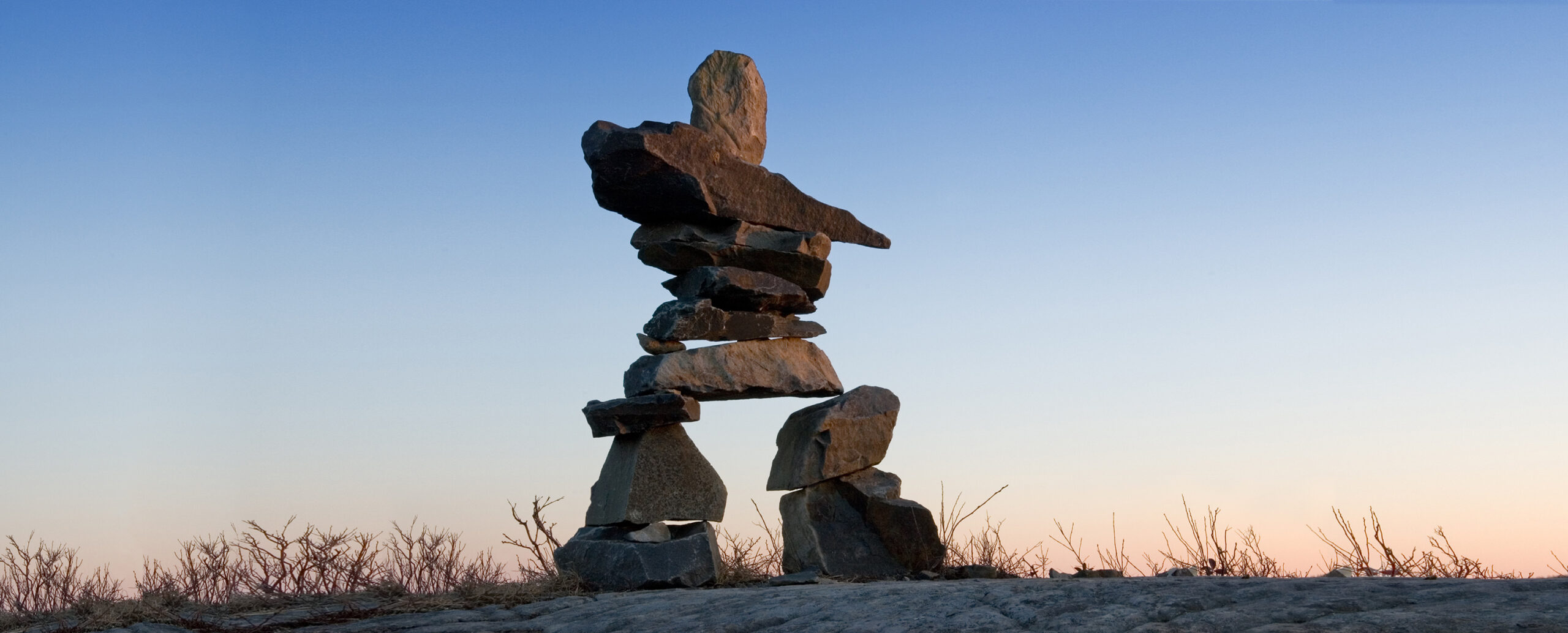 Inuksuk is a manmade stone landmark built by the Inuit people. Found above the Arctic Circle, a region dominated by the tundra biome with few natural landmarks, these structures once served as a compass. The presence of an Inuksuk might indicate a hunting area, a sacred place, or act as a navigator for travellers. In a vast, barren region where much of the landscape looks the same, Inuksuk provided evidence that travellers weren't alone, that someone had previously stood where they stood. Today Inuksuk symbolizes guidance, orientation and shared knowledge for the common good.
